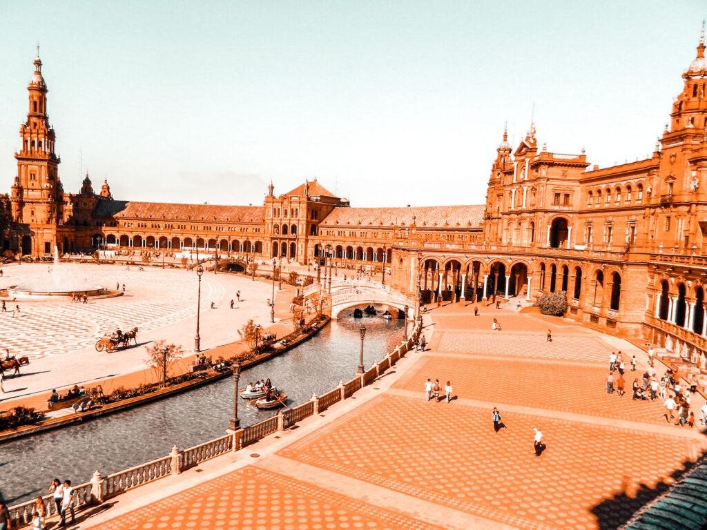 Plac Hiszpański Sewilla, zabytek, miejsce do odwiedzenia w Sewilli, piękny, ogromny plac na planie półkola z kanałem po środku, mostami i fontanną na środku.